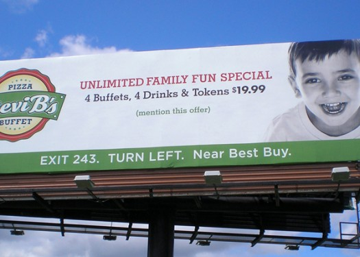 """Billboards do double duty to sell """"weird"""" pizza & help kids in need"""