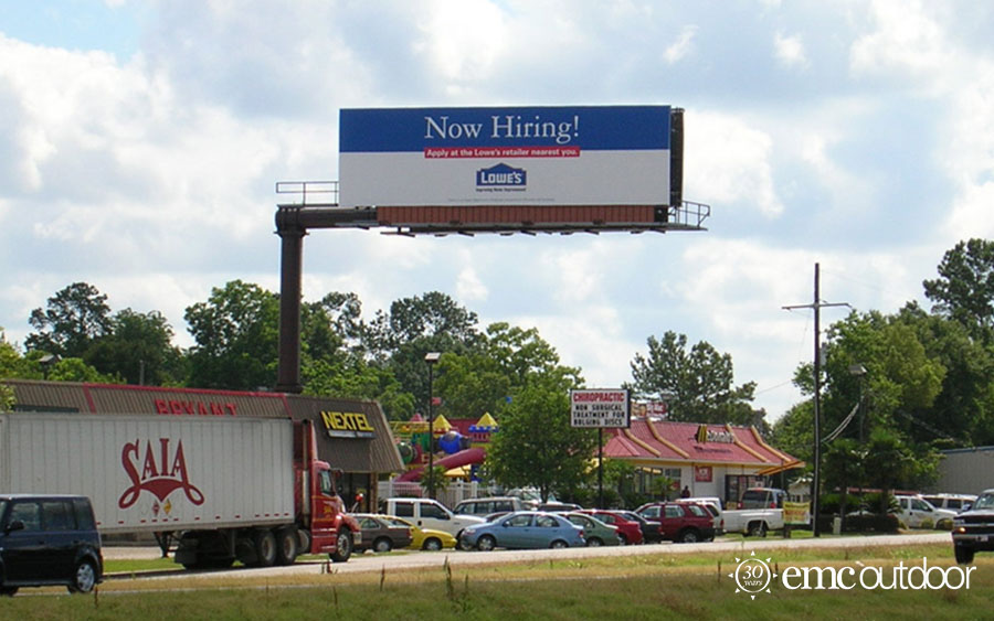 A billboard featuring a Now Hiring message