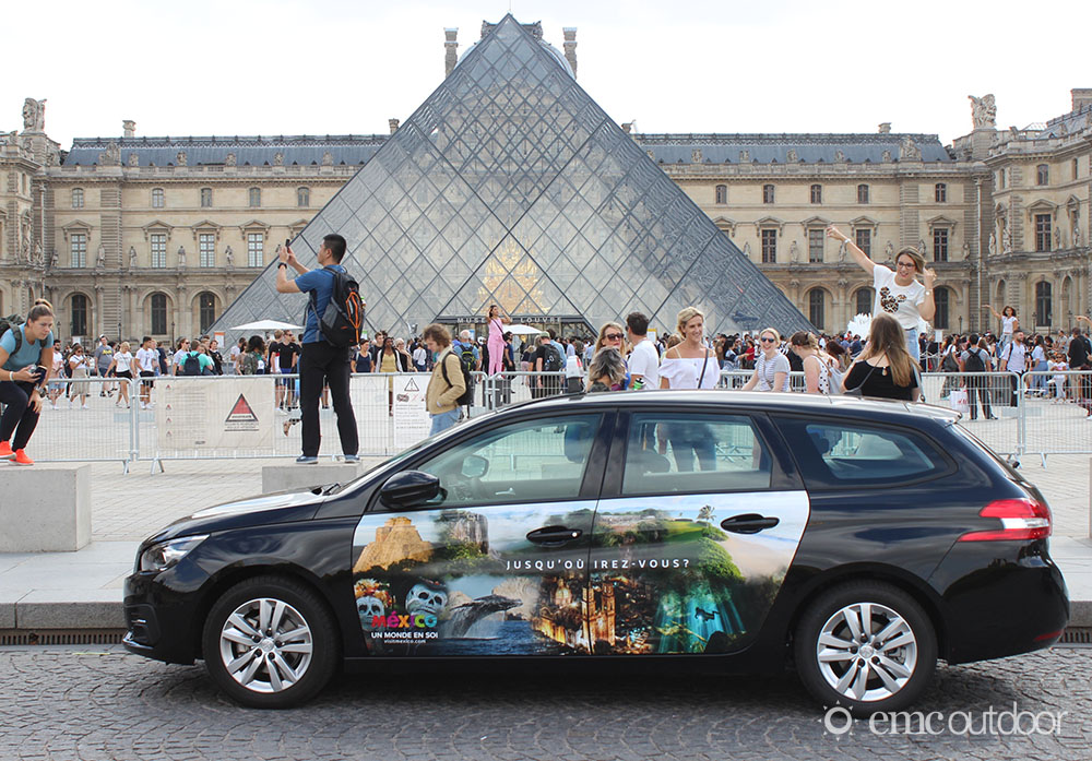A wrapped vehicle in front of the Louvre displaying advertising for a tourism desitination