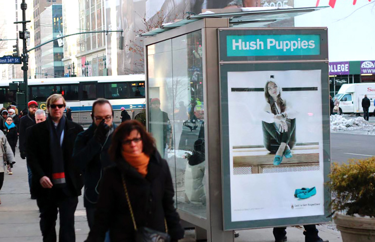 Image of a transit shelter ad in an urban setting used to promote a retail apparel brand
