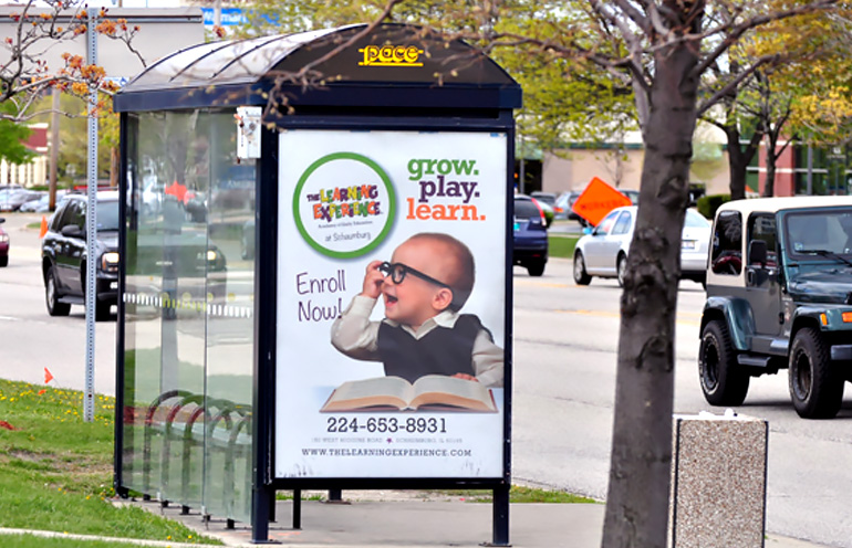 Image of bus shelter ad in a suburban environment for an education advertiser
