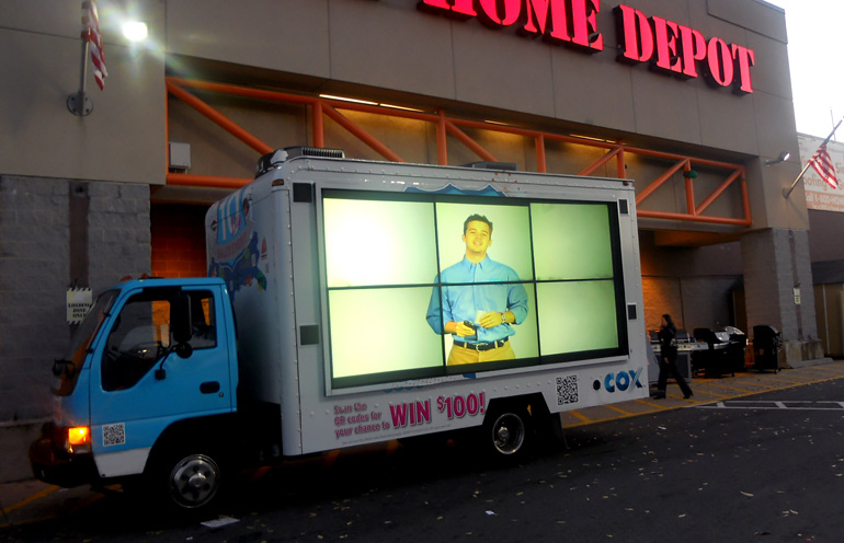 Image of a video display vehicle targeting customers at a retail location